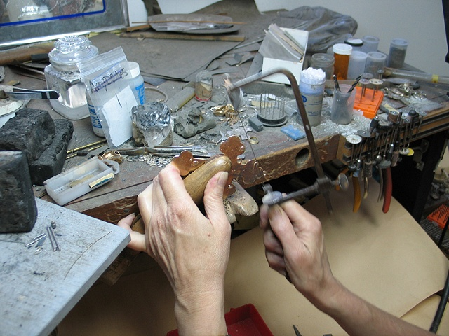 SAWING THE SPRUE REMAINS FROM CROSS