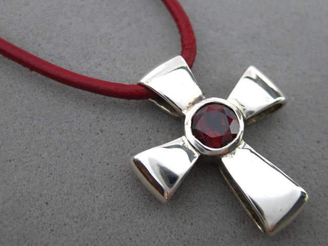 Sterling silver ribbon cross with faceted garnet ©Nancy Denmark