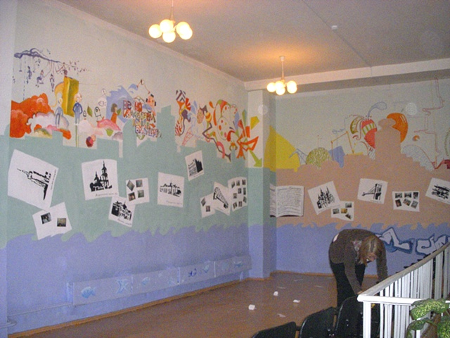 "View from back of the room, with photos of the mural process added to ""blank"" book pages"