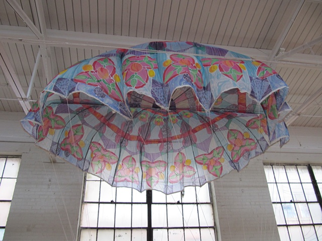 """Reentry,"" a sculpture consisting of a vintage military-issue silk parachute transformed into a fluttering leaded glass rose window."