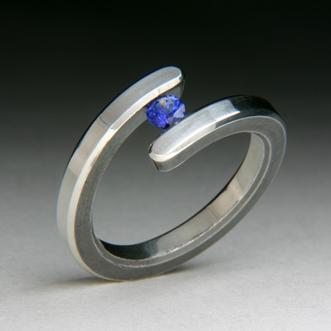 Bi-Pass Tension set ring, made of sterling silver with a high polish. Tension set stone is a blue natural sapphire.