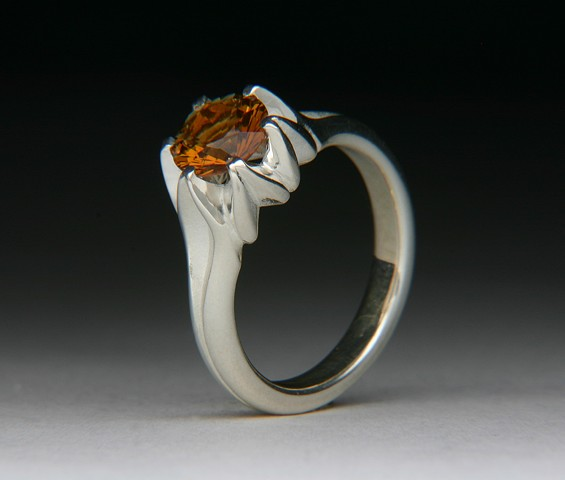 THE SMALL FULL LOTUS IS A DESIGN TWIST ON THE LARGER FULL LOTUS. IT IS THE EXACT SAME RING JUST SMALLER. THE MOUTNING IS DE-OX SILVER THAT DOESN'T TARNISH LIKE STERLING SILVER. SET WITH AN AMAZING MADERA ORANGE CITRINE.