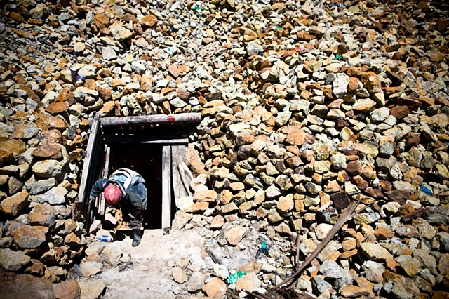 A young miner coming out of his 8-hour shift, carrying 40 kgs. of mineral in his back. His working area is some 100 mts. below from this point where the temperature rises to 38ºC and the oxygen levels drop drastically.