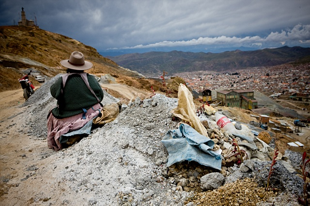A woman works breaking stones and getting the little mineral attached to them. These women are usually widows that have lost their husbands in the mines.