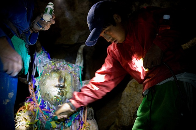 "A former miner explains Marvin (14) about the traditions that have to be carried out inside the mine. Marvin pours alcohol and spreads coca leaves on the ""tio"" devil guardian of the mine)"