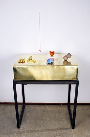 This still-life is assembled out of hand-made objects, displayed on a heated brass box. The box acts as a body, and the objects are like jewelry.