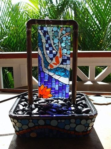 Mosaic fountain with koi and lotus created from scrap stained glass, recycled dishware and millefiore.
