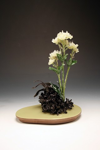 Hand formed black clay and resin dipped silk flowers on a walnut base