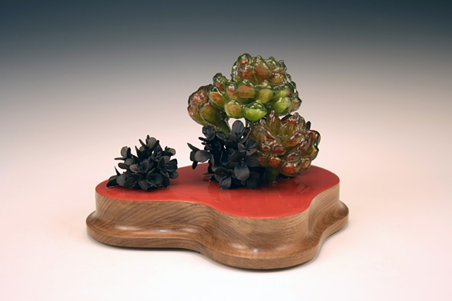 small still life with had built black clay flowers and resin dipped flowers