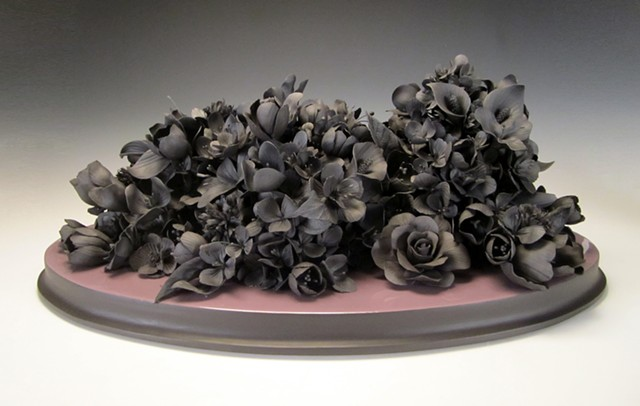 Hand built black clay sculpture on a resin coated milled wood base