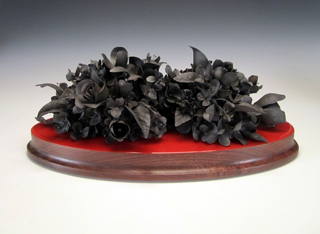 This still life sculpture if made from many handformed, mid-range black clay flowers.