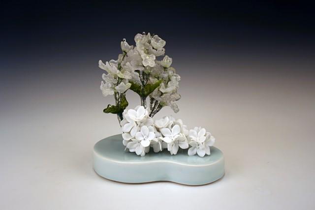 porcelain and resin dipped silk flower sculpture on a blue glazed porcelain base