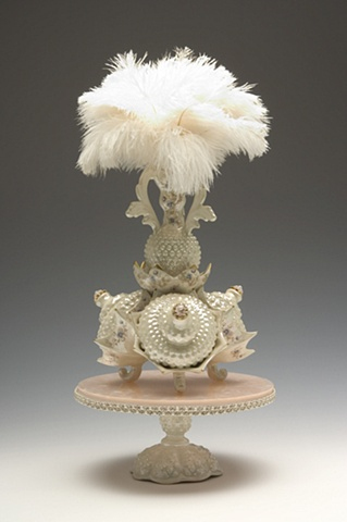 pink and cream feathered porcelain sculpture with vintage decals on a plexiglass stand