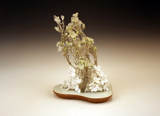 white porcelain sculpture with resin dipped silk flowers on a walnut base