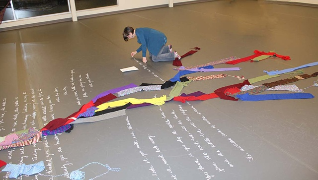 "Transcribing the poem ""Unraveling"" onto the gallery floor with chalk."